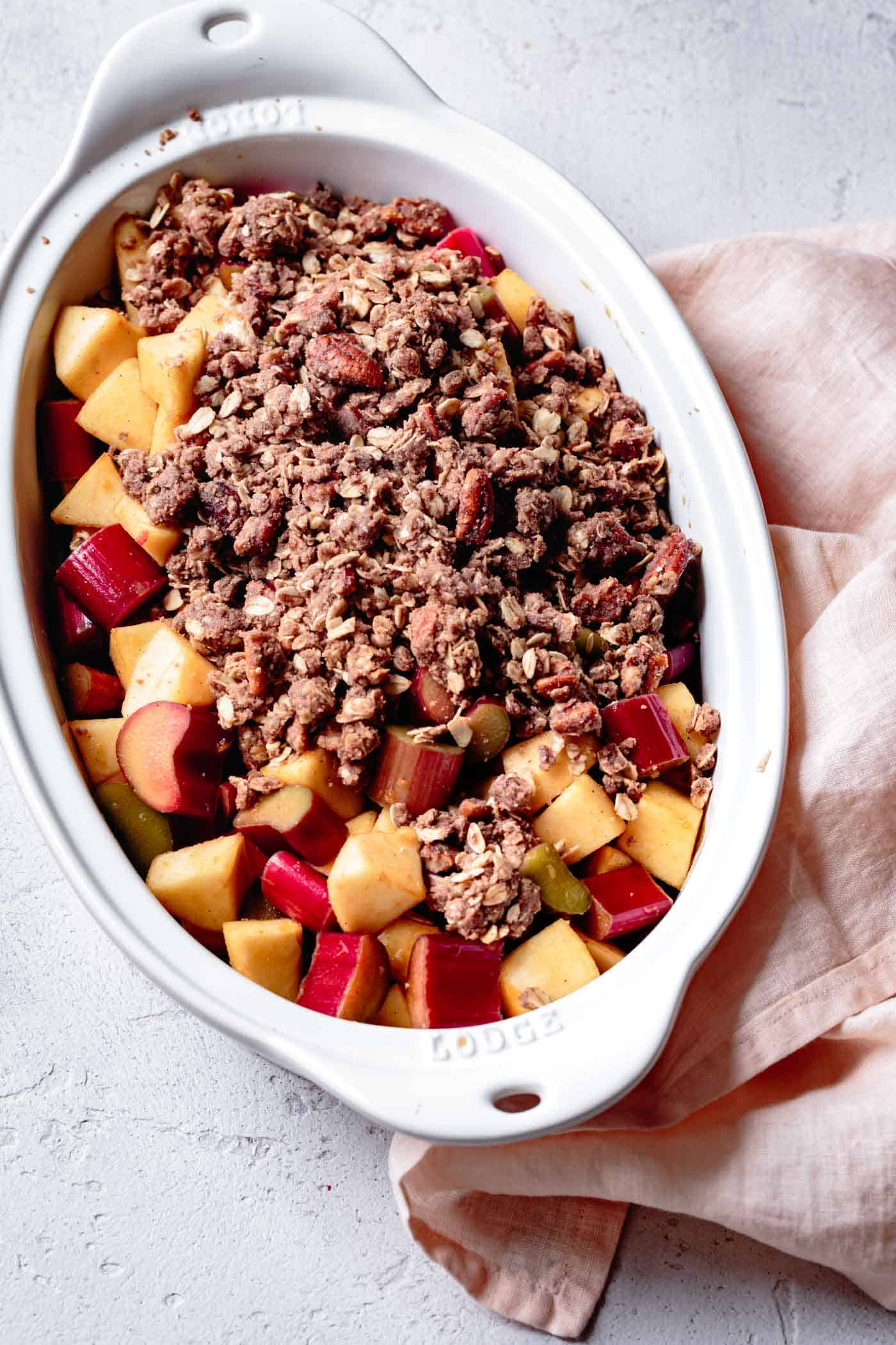 unbaked apple rhubarb crisp with oatmeal in a baking dish