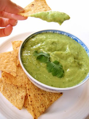 chip being dipped into avocado salsa