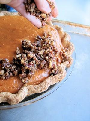 pecans being sprinkled onto pie