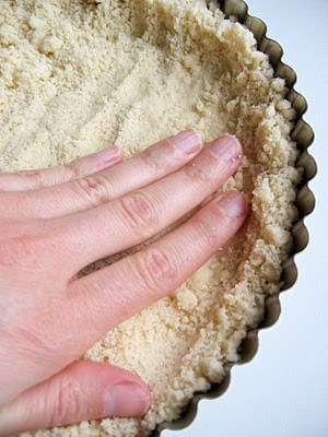hand pressing down tart crust