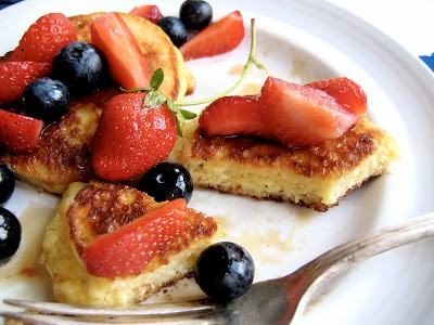 sliced ricotta pancake on a plate with fruit