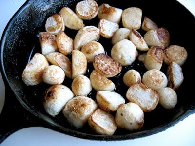 a skillet full of turnips cooking