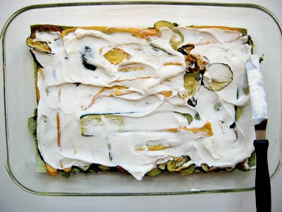 top down shot of cheese being spread onto vegetable layer in baking dish