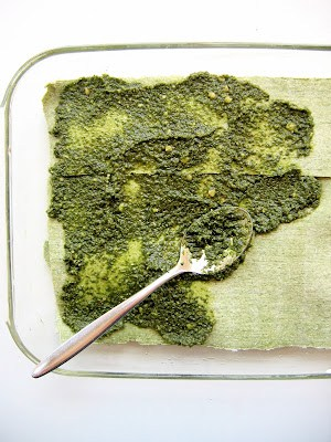 pesto being spread onto lasagna layer