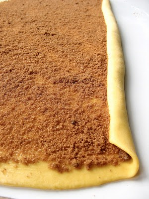 sheet of dough with sugar and cinnamon spread on it
