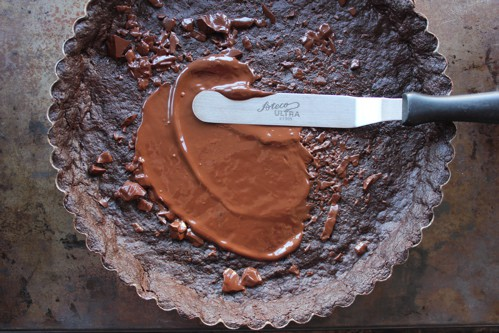 chocolate being spread on a tart