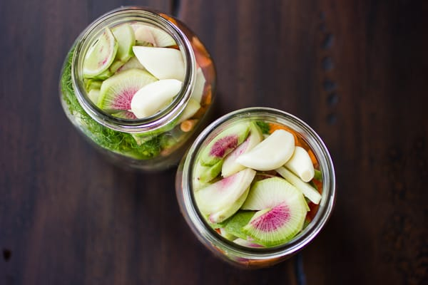 top down shot of carrot and watermelon radish pickle in jars