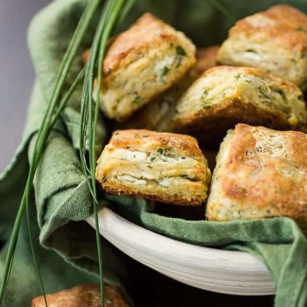 a bowl full of cheese and chive biscuits