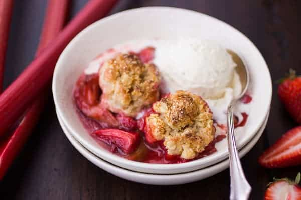 strawberry rhubarb cobbler in a bowl with melty ice cream