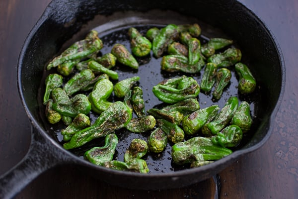 padron peppers cooking in a skillet