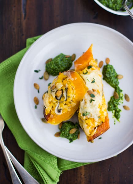 Vegetarian Stuffed Butternut Squash with Mushrooms, Millet, and Kale Pesto on a plate