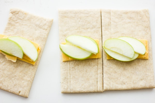 apple and slice of cheese on pastry sheet