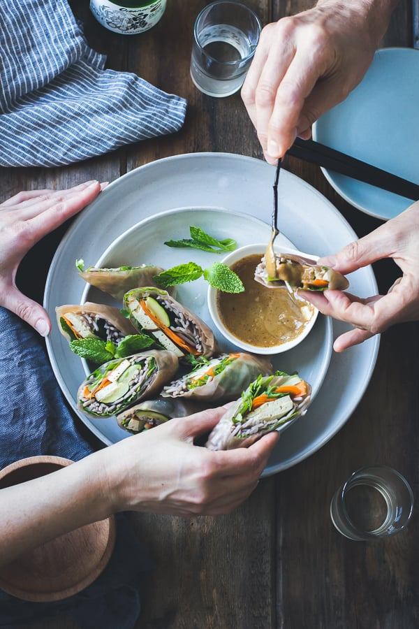 People putting dipping sauce on Roasted Zucchini + Soba Noodle Summer Rolls {Vegan + Gluten-Free}
