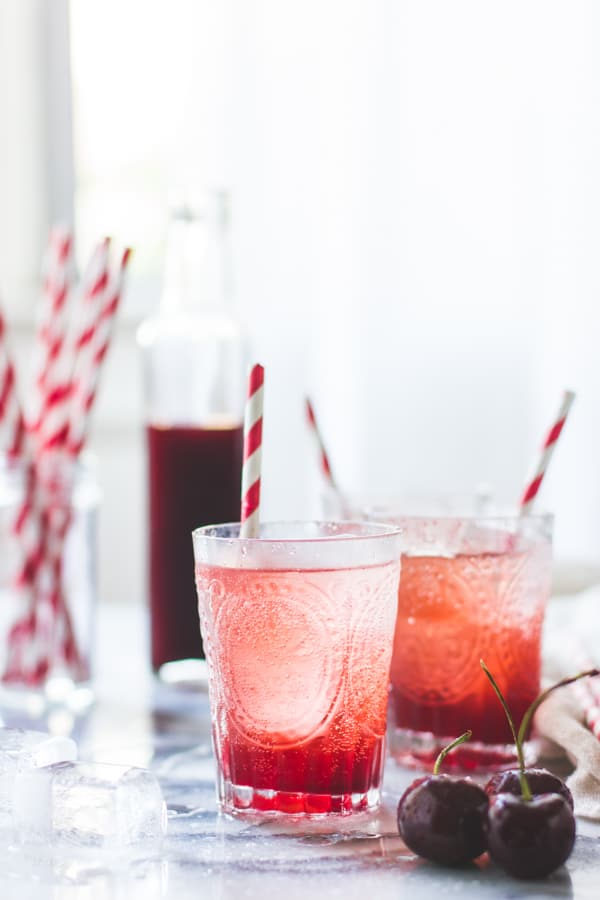 shot of two glasses of Cherry Vanilla Maple Shrub {Drinking Vinegar}