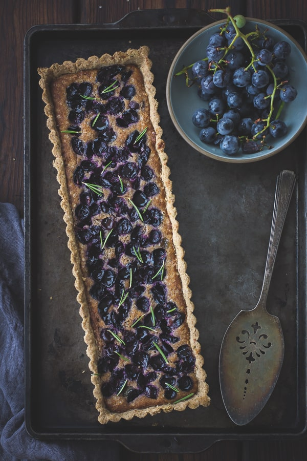 top down shot of Concord Grape + Walnut Frangipane Tart with a Gluten-Free Rosemary Crust