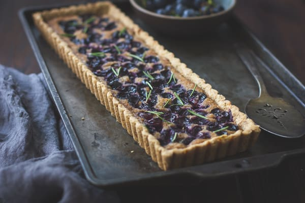side shot of Concord Grape + Walnut Frangipane Tart with a Gluten-Free Rosemary Crust