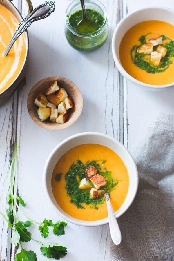 bowl of Roasted Yellow Tomato Soup with Green Harissa + Halloumi Croutons