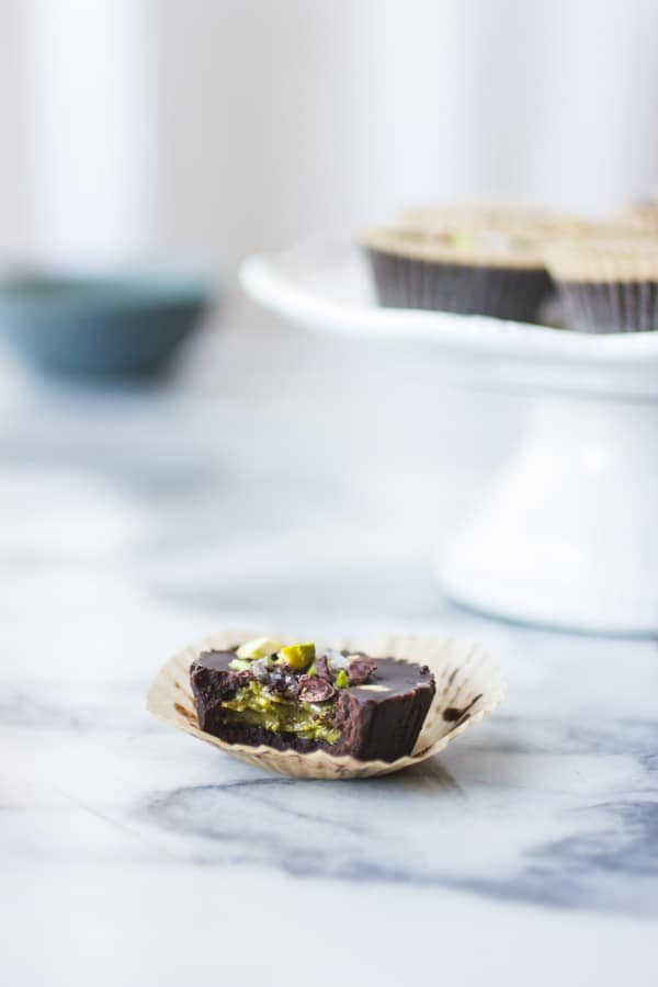 Raw Chocolate + Pistachio Butter Cups with bite taken out