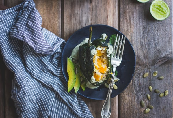 Roasted Poblano Chiles Stuffed with Cheesy Butternut Squash Quinoa + Pepita Crema on a plate