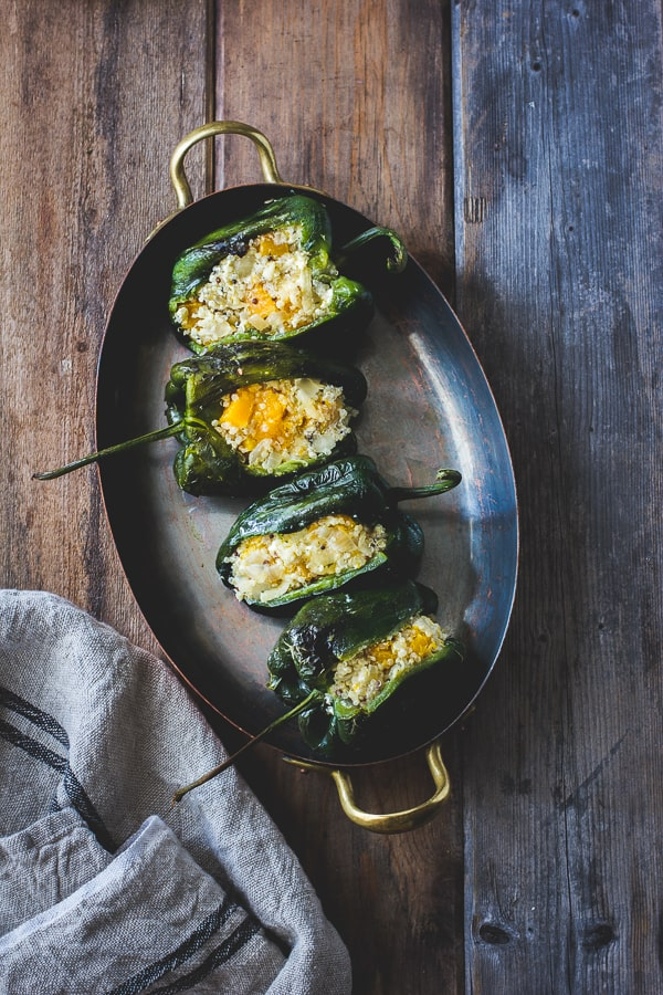 Roasted Poblano Chiles Stuffed with Cheesy Butternut Squash Quinoa + Pepita Crema on table