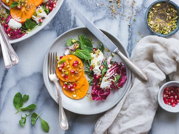 Persimmon + Pomegranate Salad with Burrata + Pistachio Dukkah on plate