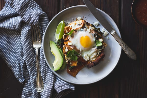 Baked Chilaquiles with Black Beans and Kale on a plate with knife and fork