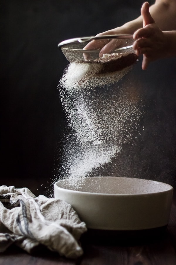 sieving ingredients into bowl