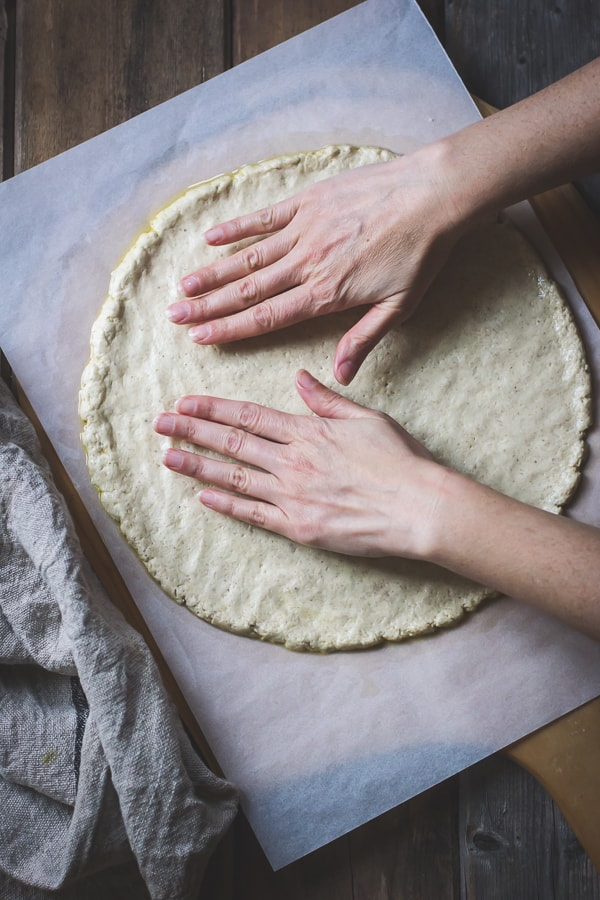 hands flattening Gluten-Free Pizza Crust