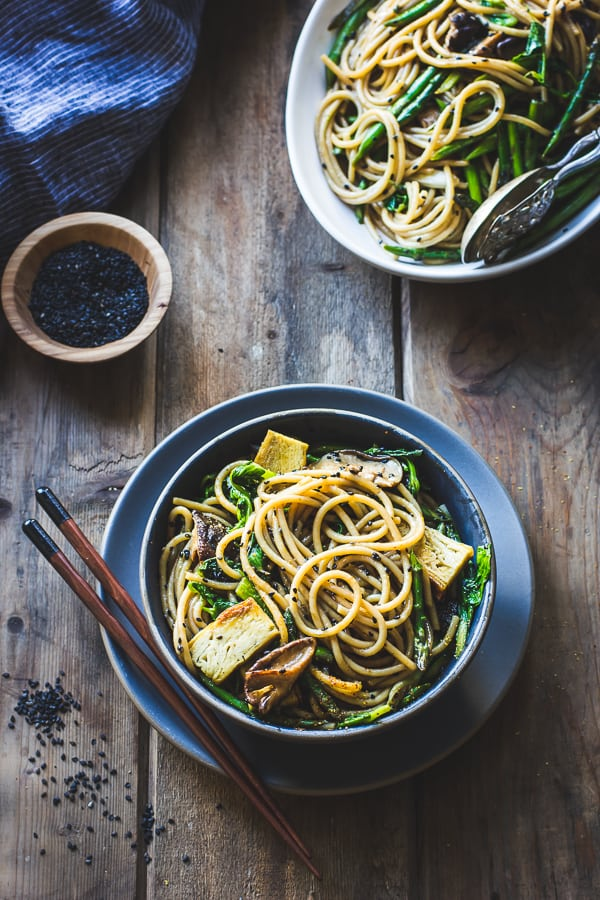 Hot Sesame Rice Noodles with Asparagus, Shiitakes and Pea Shoots with chopsticks