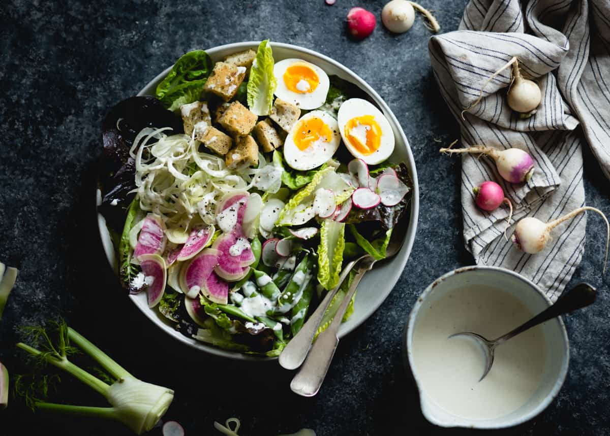 bowl of spring greens salad with fennel, radish, and miso-buttermilk dressing
