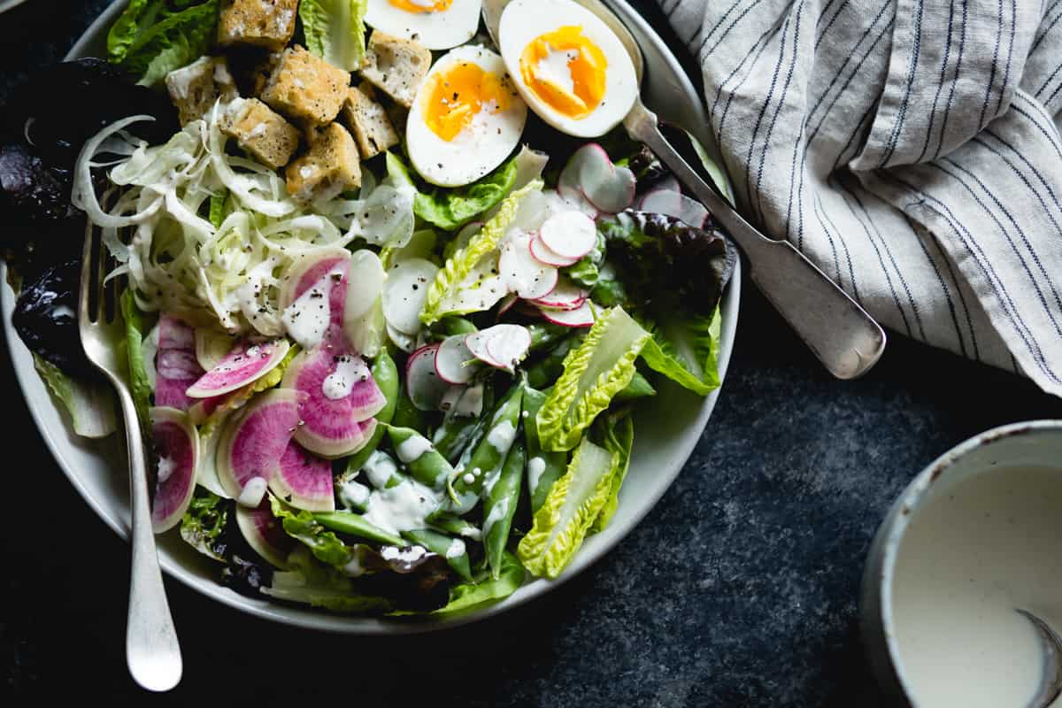big bowl of spring greens salad with fennel, radish, and miso-buttermilk dressing
