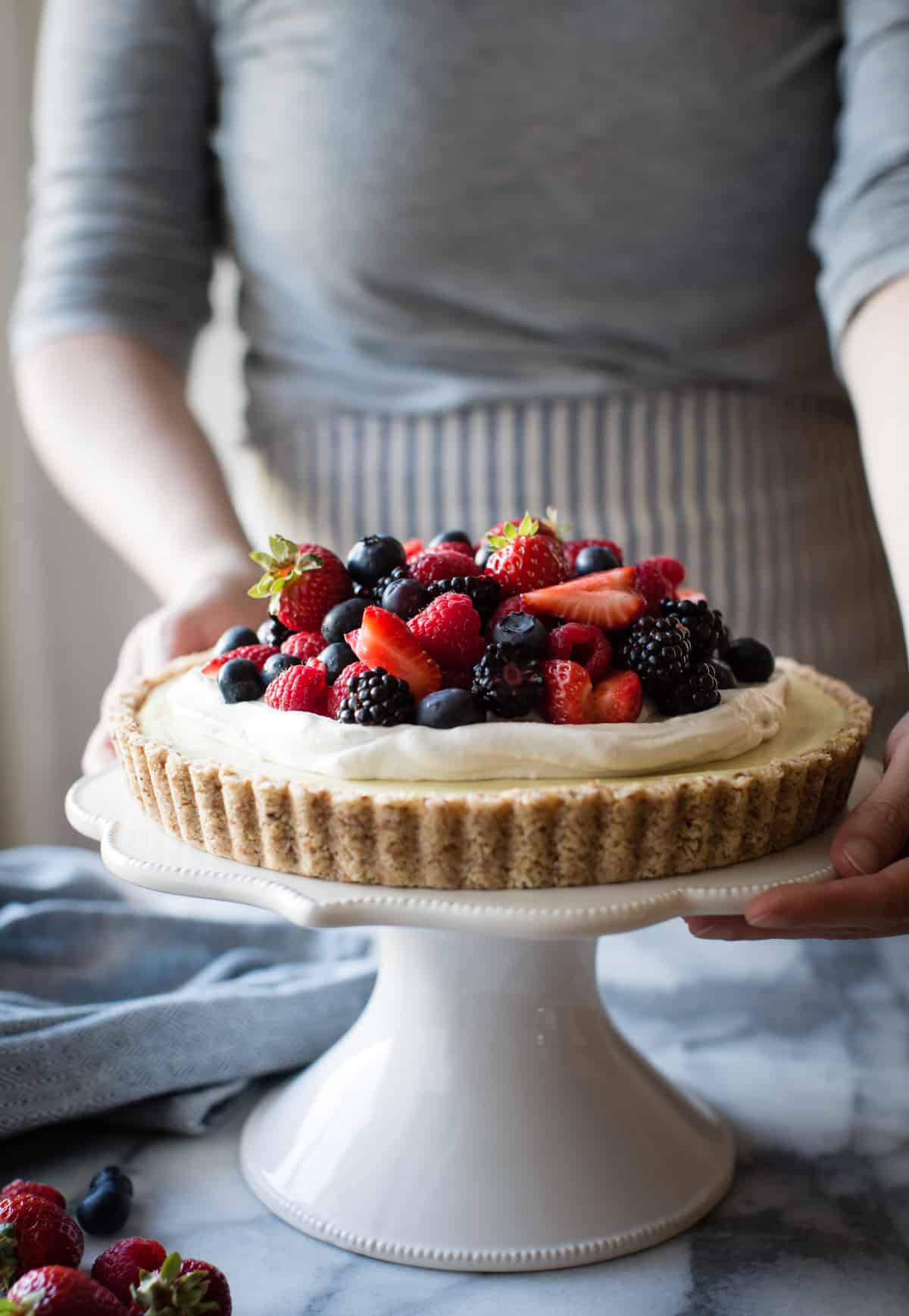 hands holding No-Bake Lemon Berry Coconut Cream Tart {vegan, gluten-free, refined sugar-free}