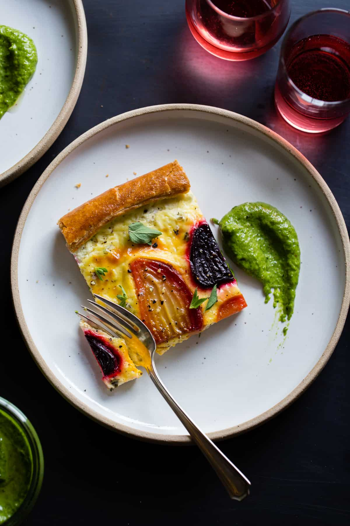 fork cutting into Ricotta Beet Tart with Beet Green Pesto