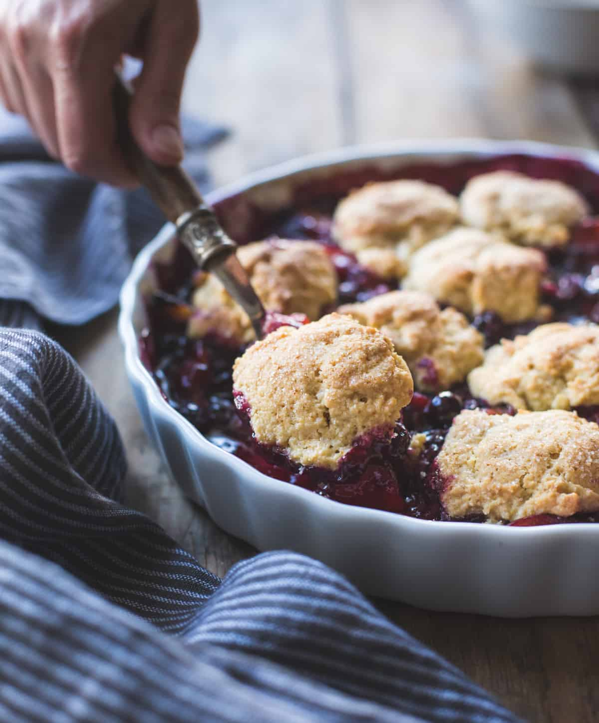 scooping Gluten-Free Blueberry Plum Cobbler with Corn Flour Biscuits