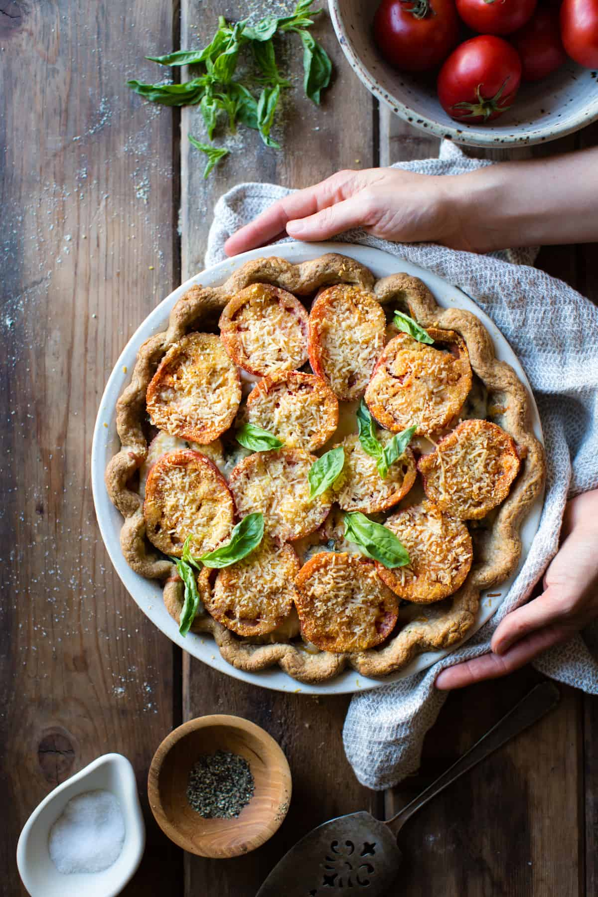 hands holding Tomato Pie with Basil, Parmesan + Cornmeal {gluten-free}