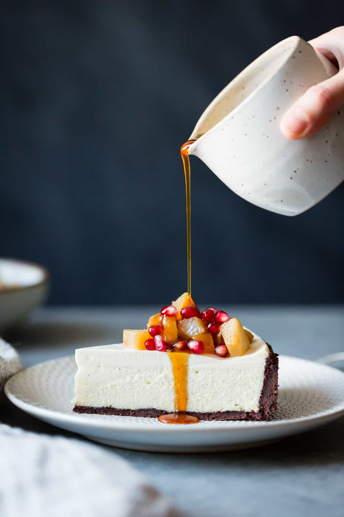 drizzling sauce on Chocolate Crusted Chèvre Cheesecake with Earl Grey Poached Pears & Pomegranate {gluten-free}