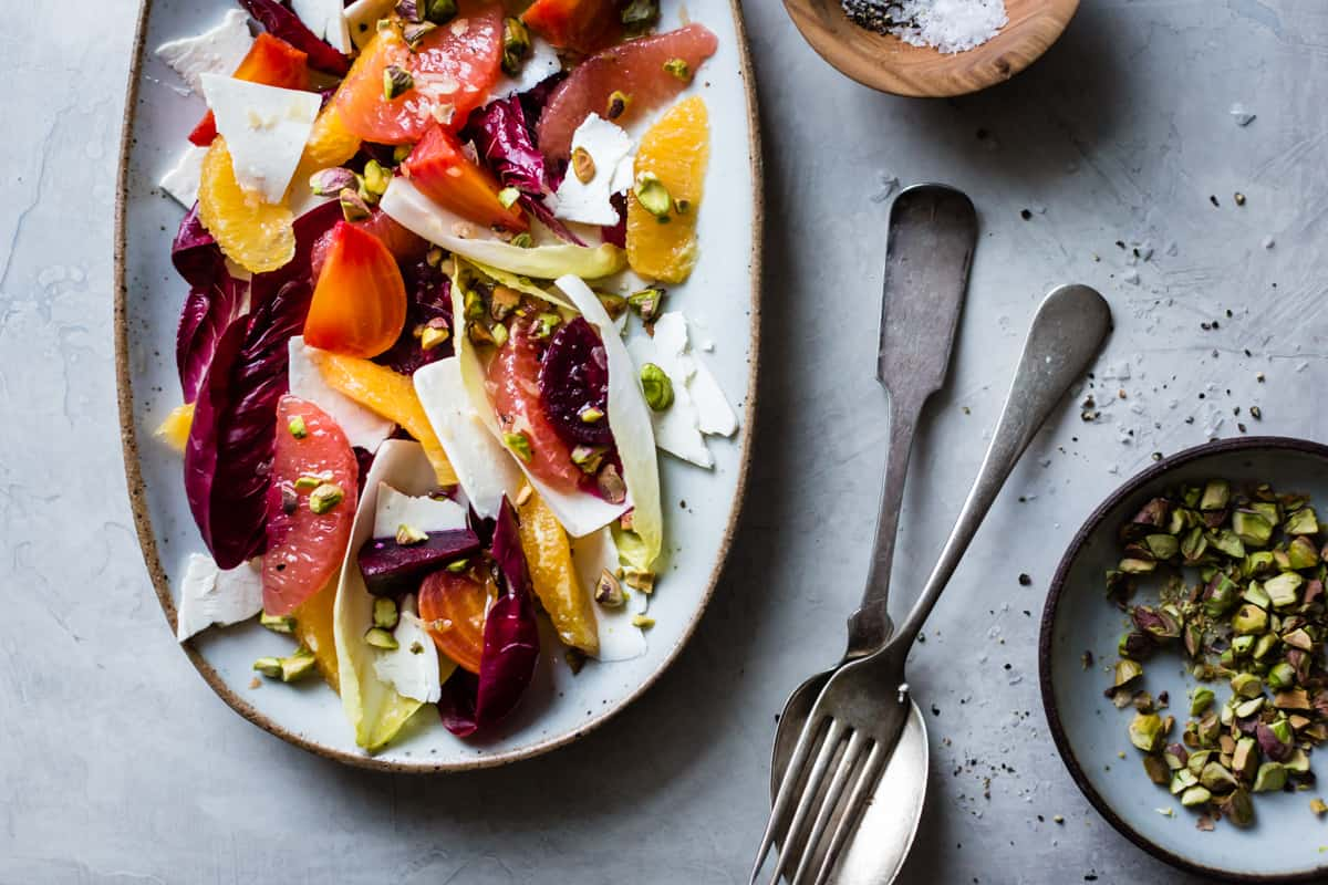 Beet, Citrus, & Chicory Salad with Ricotta Salata and Pistachios on table