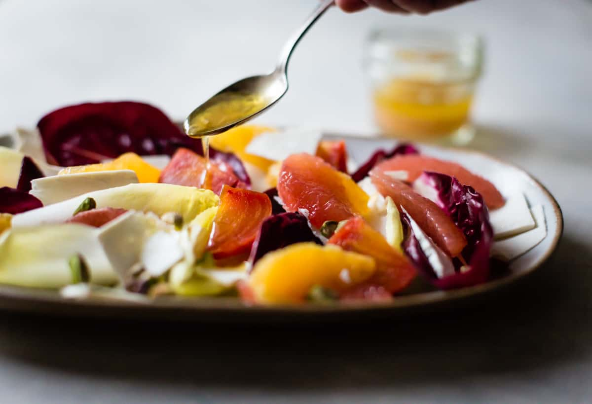 drizzling dressing on Beet, Citrus, & Chicory Salad with Ricotta Salata and Pistachios