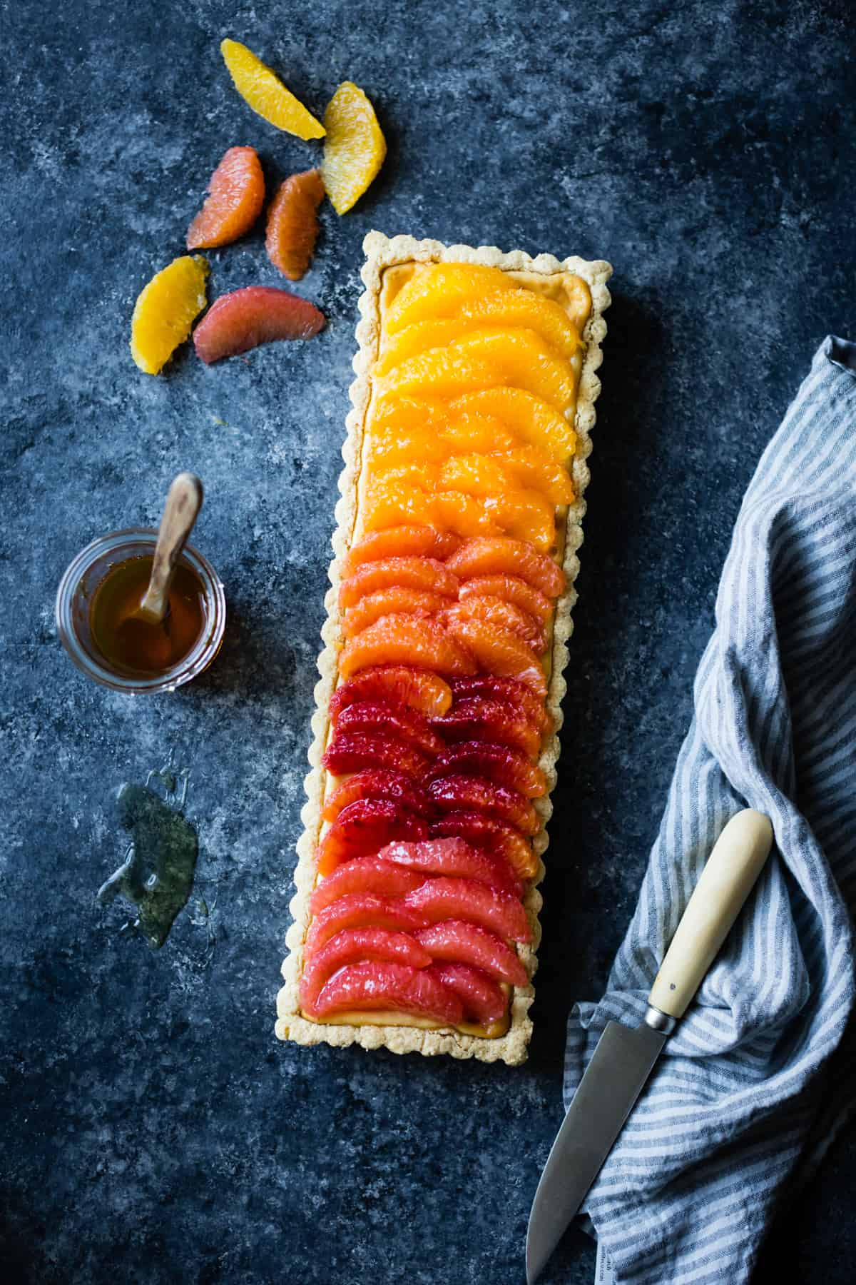 Gluten-Free Citrus Ricotta Tart with Almond Corn Flour Crust on table with slices of citrus
