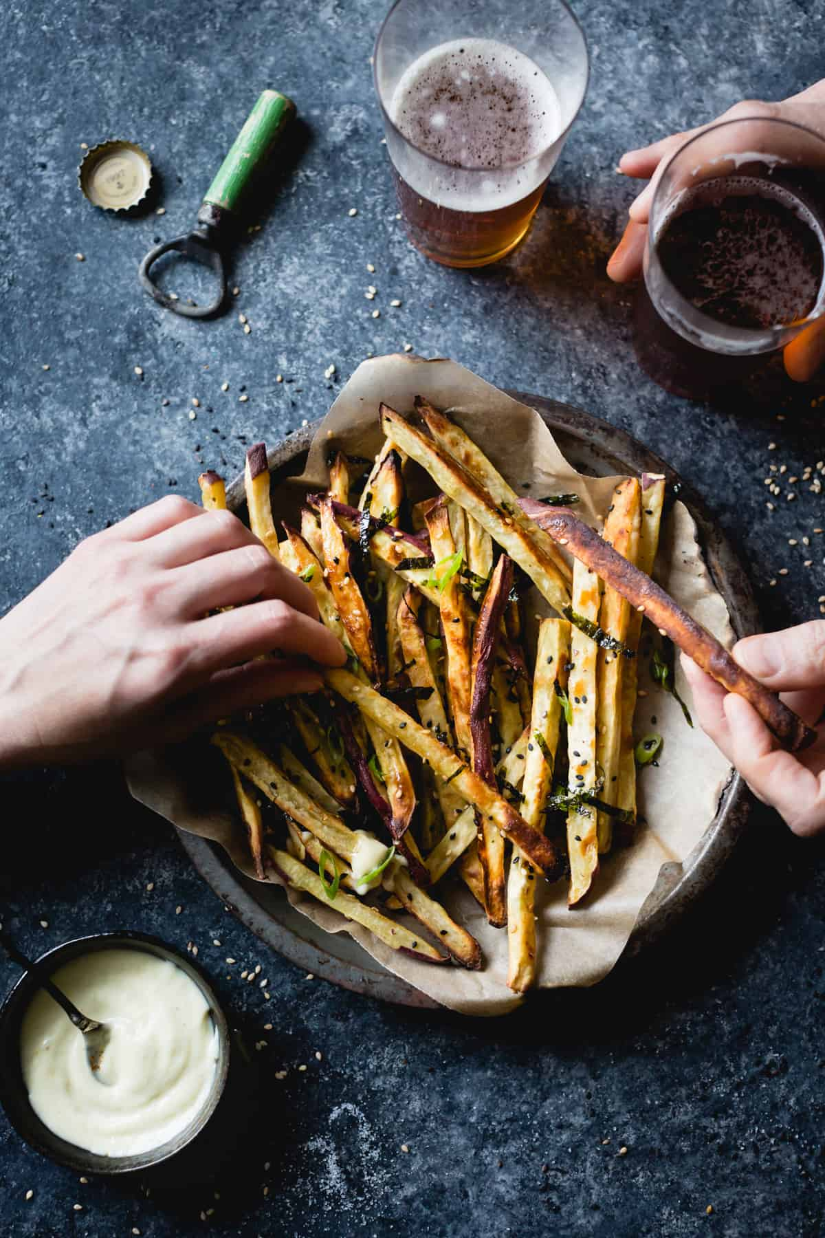 hands picking up some Japanese Sweet Potato Oven Fries with Wasabi Aioli