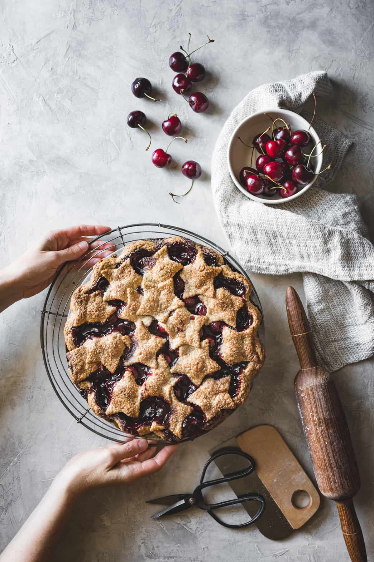 hands placing Spiced Bourbon Cherry Pie {gluten-free} on wire rack