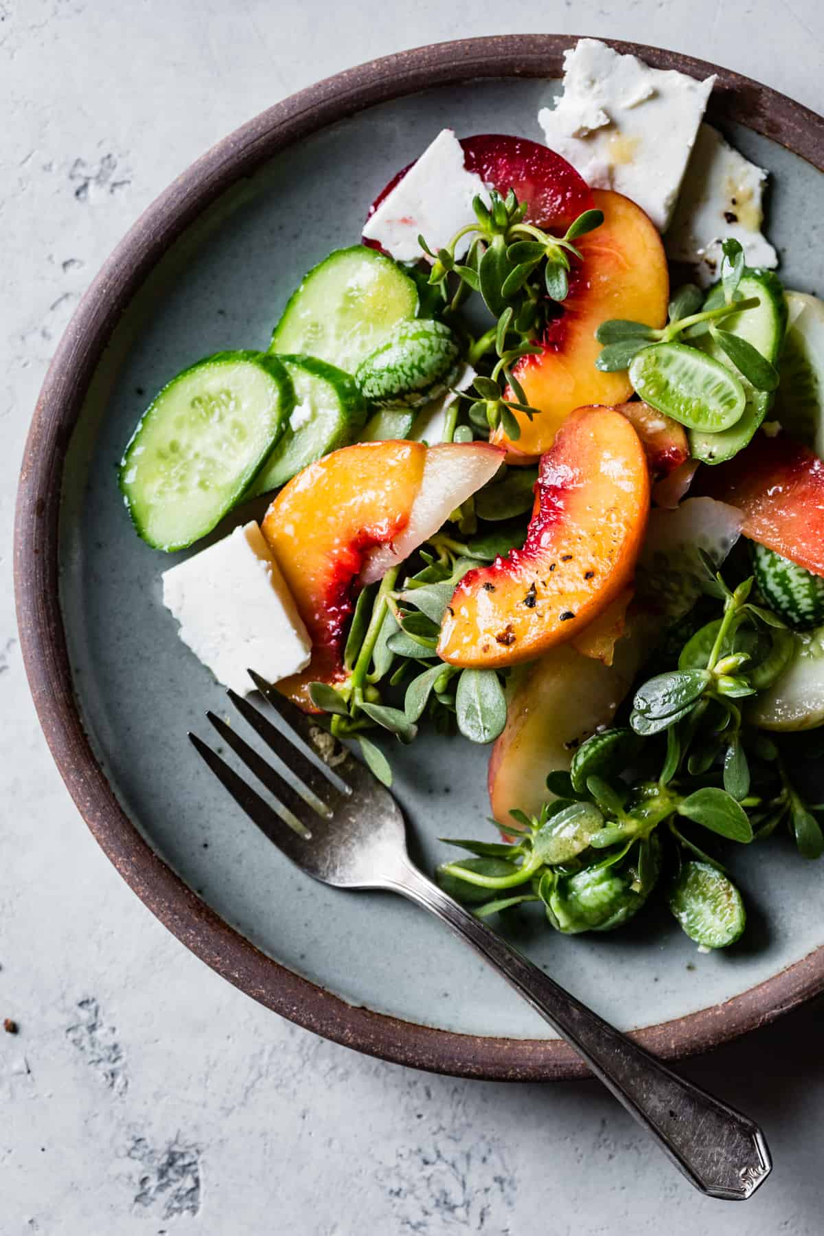 Stone Fruit Cucumber Salad with Ricotta Salata, Purslane, and Golden Balsamic Miso Vinaigrette on plate