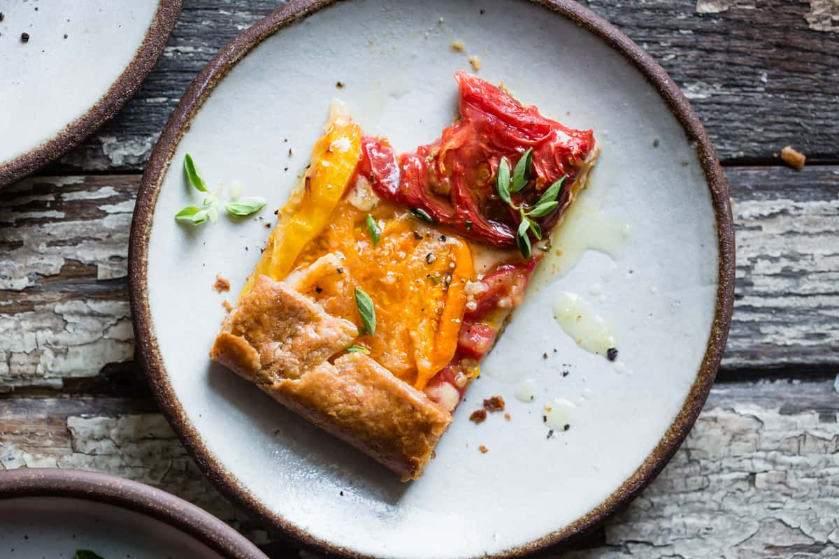 slice of Rustic Heirloom Tomato Tart {gluten-free} with bite taken out