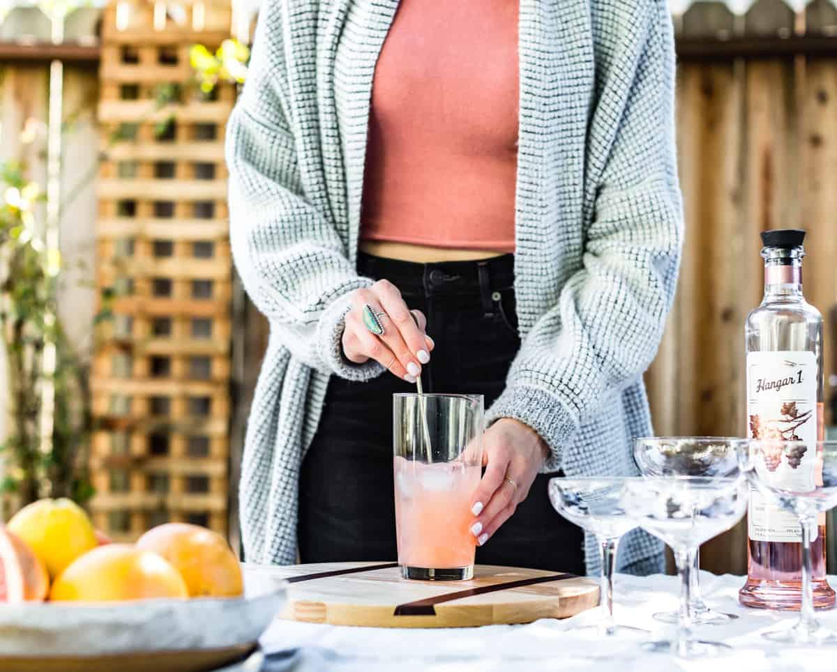 someone stirring Sparkling Grapefruit, Elderflower & Rosé Vodka Cocktails
