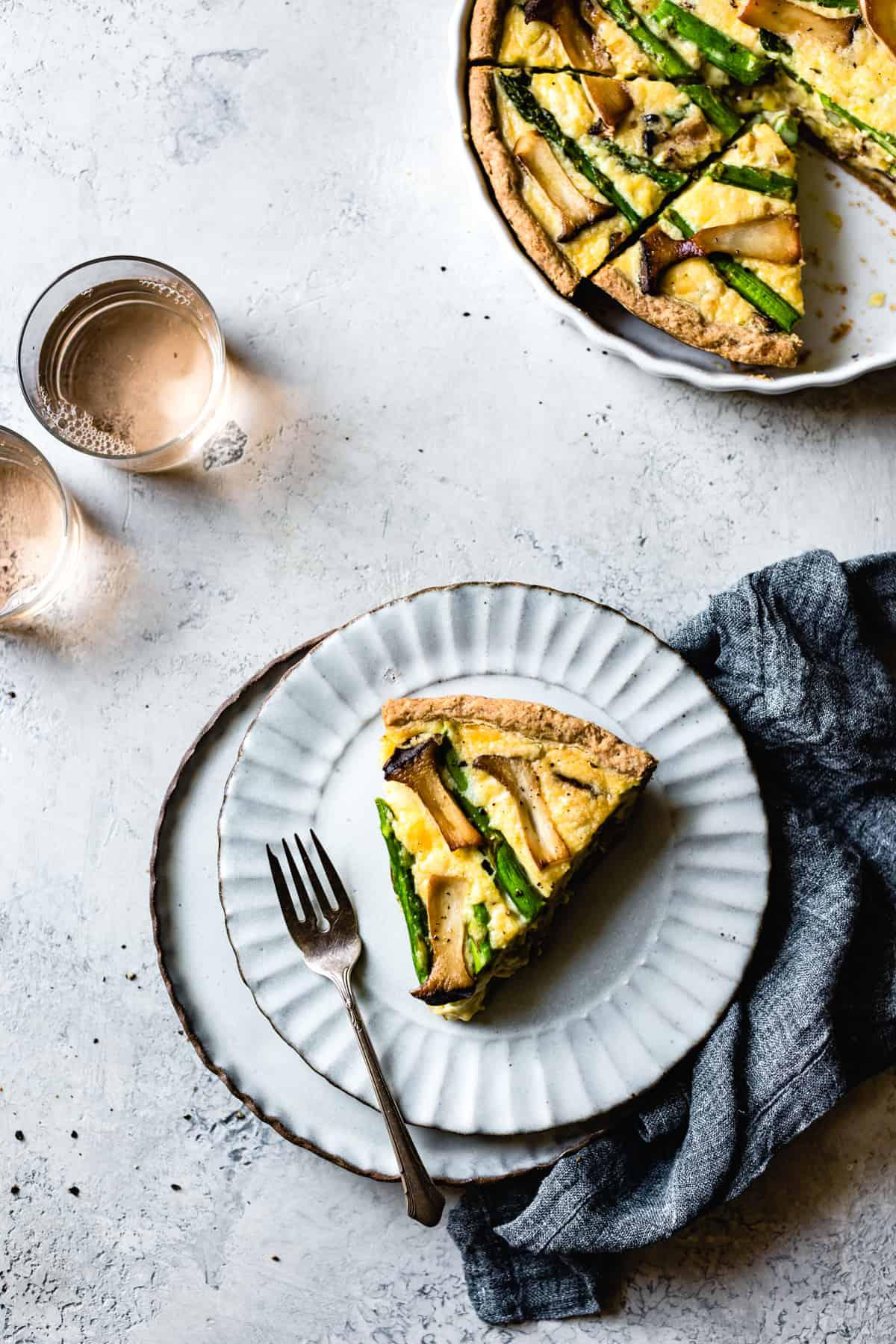 a slice of Cheddar Mushroom Asparagus Quiche & Gluten-Free Ghee Piecrust