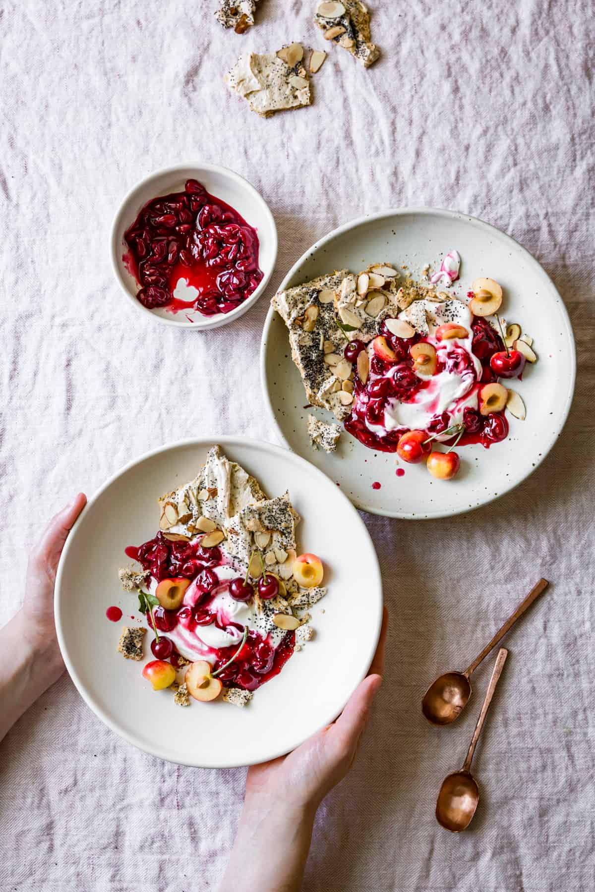 hands holding Tart Cherry Eton Mess with Poppy Seed Almond Meringues