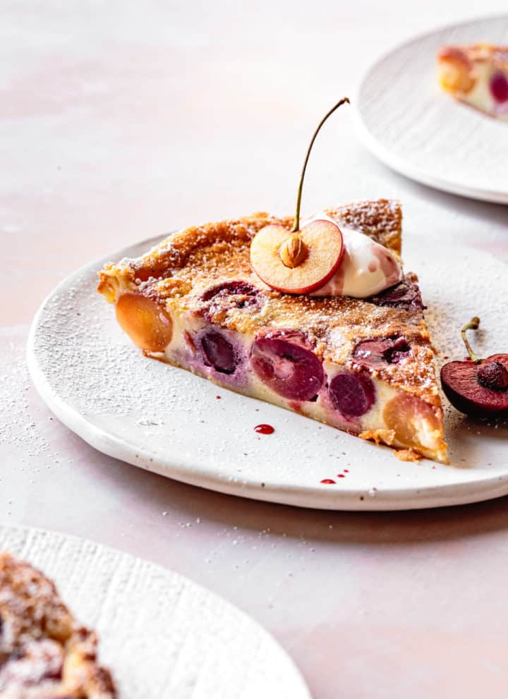 Gluten Free Cherry Clafoutis slice on a plate with creme fraiche