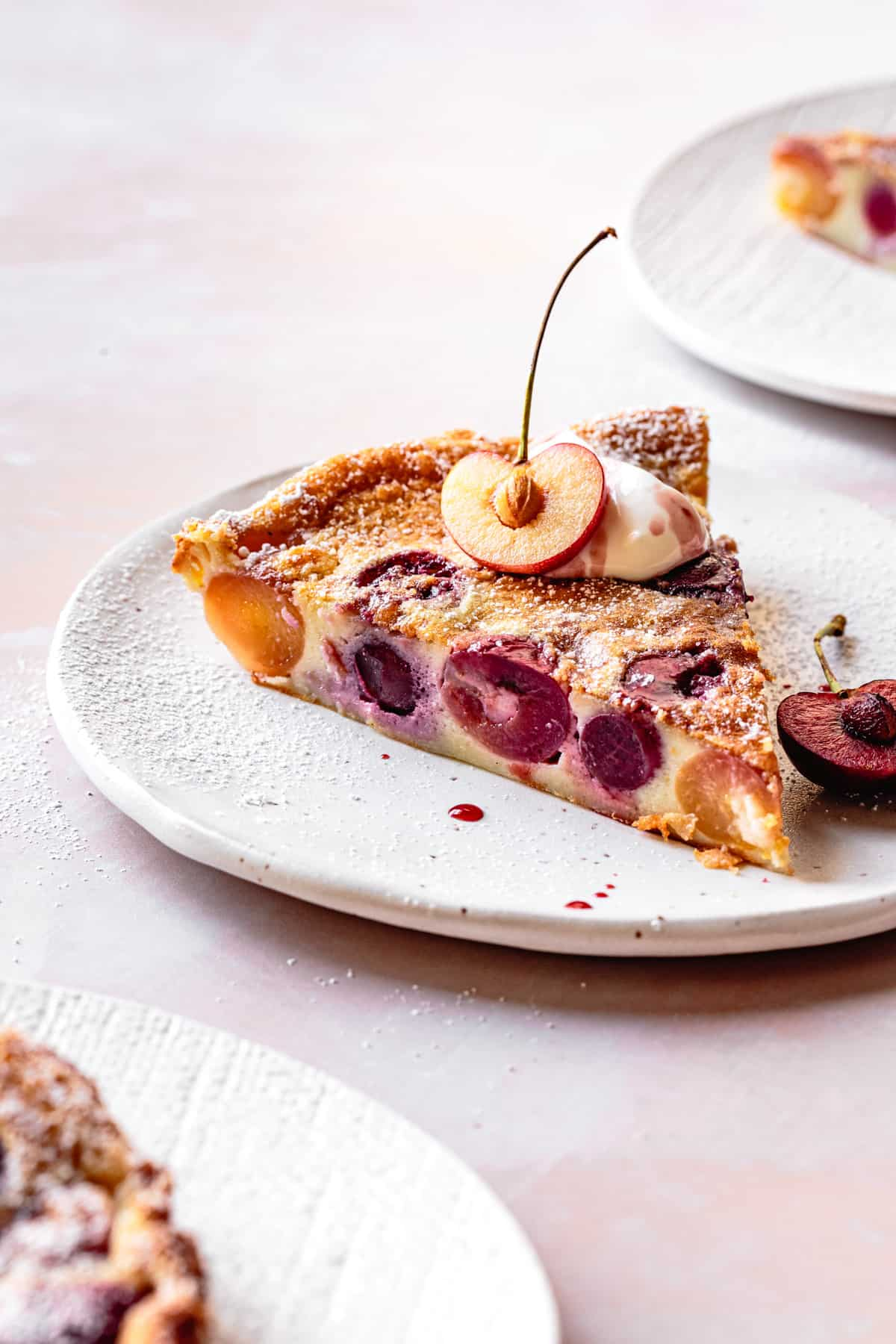 Gluten-Free Cherry Clafoutis slice on a plate with creme fraiche and sliced cherry on top