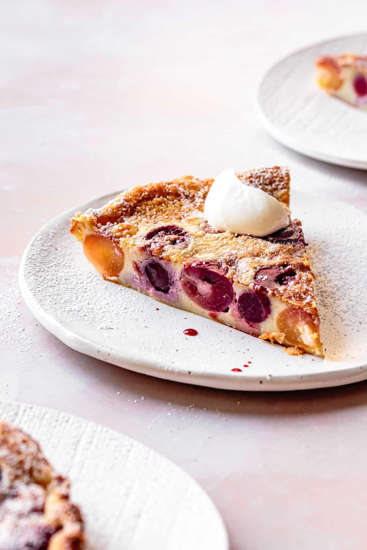 close up of Gluten-Free Cherry Clafoutis slice on a plate with creme fraiche
