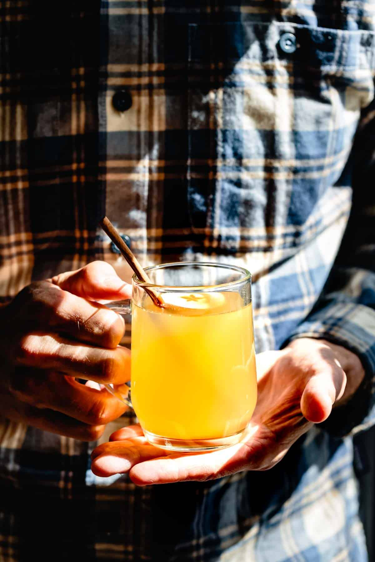 man holding a cozy apple cider vodka toddy drink